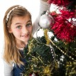 Festive little girl decorating christmas tree — Stok fotoğraf #57254887