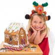 Festive little girl making gingerbread house — Foto Stock #57254921
