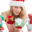 Woman in santa hat laying on the floor while holding gifts — Foto Stock #57255885