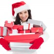 Smiling brunette in santa hat holding stack of presents — Stock Photo #57255939