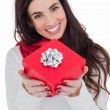 Happy brunette showing red gift with a bow  — Stock Photo #57256075
