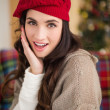 Surprised brunette on the couch at christmas — Stock Photo #57256487