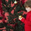 Festive little boy hanging a bauble — Stock Photo #57256801