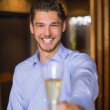 Handsome man holding flute of champagne — Stock Photo #57258307