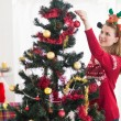 Young woman decorating a Christmas tree — Stock Photo #57258971