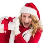 Pretty santa girl smiling at camera holding gift — Stock Photo #57259975