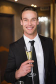 Handsome man holding flute of champagne — Stock Photo