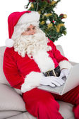 Father christmas using laptop on the sofa — Foto Stock