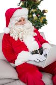 Father christmas using laptop on the sofa — Stock Photo