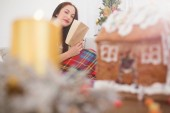 Cheerful brunette reading on the couch with cover at christmas — Stock Photo