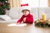 Festive little boy writing wish list — Стоковое фото