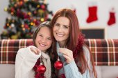 Festive mother and daughter holding baubles — Stok fotoğraf