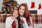 Festive mother and daughter holding baubles — Stock Photo
