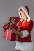 Pretty santa girl opening a gift — Stock Photo