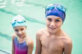 Cute little siblings standing poolside — Stock Photo
