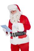 Santa claus using digital tablet — Stock Photo