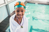 Boy wrapped in towel with medal poolside — Stock Photo