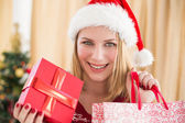 Festive blonde showing a gift while looking at camera — Foto de Stock