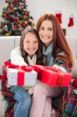 Festive mother and daughter wrapped in blanket with gifts — Стоковое фото