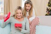 Mother opening christmas gift with daughter — Stock Photo