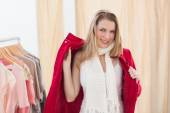 Smiling young blonde woman trying a jacket — Stock Photo