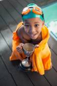 Boy wrapped in towel with trophy poolside — Stock Photo