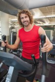 Handsome young man working out on x-trainer — Foto Stock