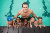 Cute swimming class in pool with coach — Photo