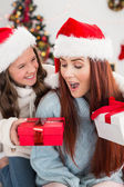Festive mother and daughter exchanging gifts — Stock Photo