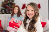 Festive little girl holding a gift — Stock Photo