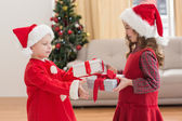 Festive little siblings holding gifts — Stock Photo