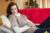 Happy brunette relaxing on the couch at christmas — Stock Photo