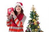 Festive brunette listening gift by the christmas tree — Stock Photo