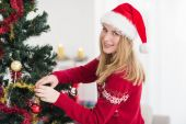 Woman decorating a Christmas tree while looking at camera — Stock Photo