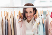 Beauty brunette smiling at camera by clothes rail — Stok fotoğraf
