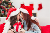Festive mother and daughter on the couch with gift — Foto Stock