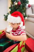Cute boy in large christmas present drinking milk — Photo