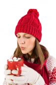 Festive girl blowing over mug — Stock Photo