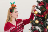 Woman hanging christmas decorations on tree — Foto de Stock