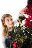Festive little girl decorating christmas tree — Stock Photo