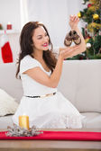 Happy brunette holding baby shoes at christmas  — Stock Photo