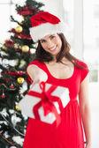 Festive brunette in red dress holding gift at christmas — Stock Photo
