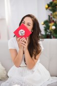 Brunette showing gift on the couch at christmas — Stock Photo