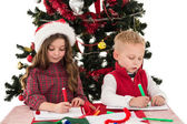 Festive little siblings drawing pictures — Stock Photo