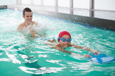 Boy learning to swim with coach — Stock Photo