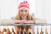 Pretty blonde smiling at camera by clothes rail — Stok fotoğraf