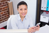 Female executive text messaging in office — Stock Photo