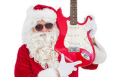 Cool santa showing electric guitar — Stockfoto