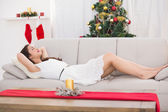 Brunette sleeping on the couch at christmas — Stockfoto