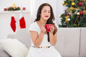 Pretty brunette enjoying a hot drink at christmas — Stock Photo